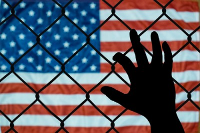 american flag with hand behind fence